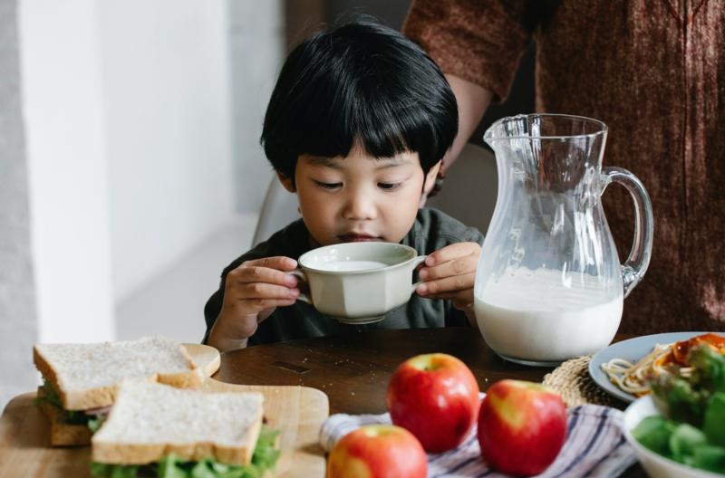 cernes sous les yeux un petit garçon qui boit du lait