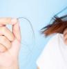 chute de cheveux femme une femme qui tient un cheveu dans sa main