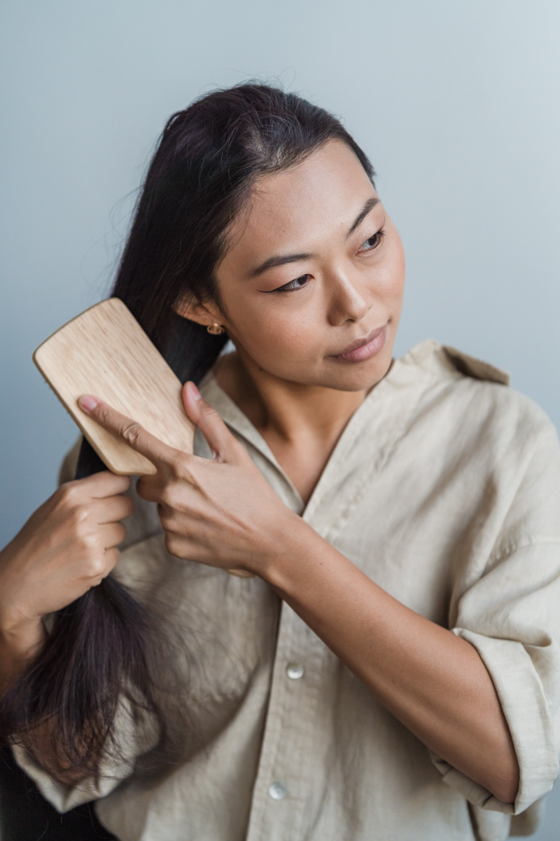 comment nettoyer une brosse à cheveux une femme qui peigne ses cheveux