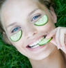 young woman with cucumber mask on face