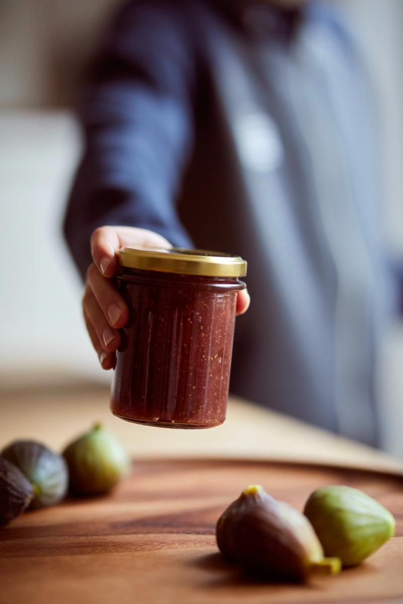 conservation figues une main qui tient un bocal de confiture de figue