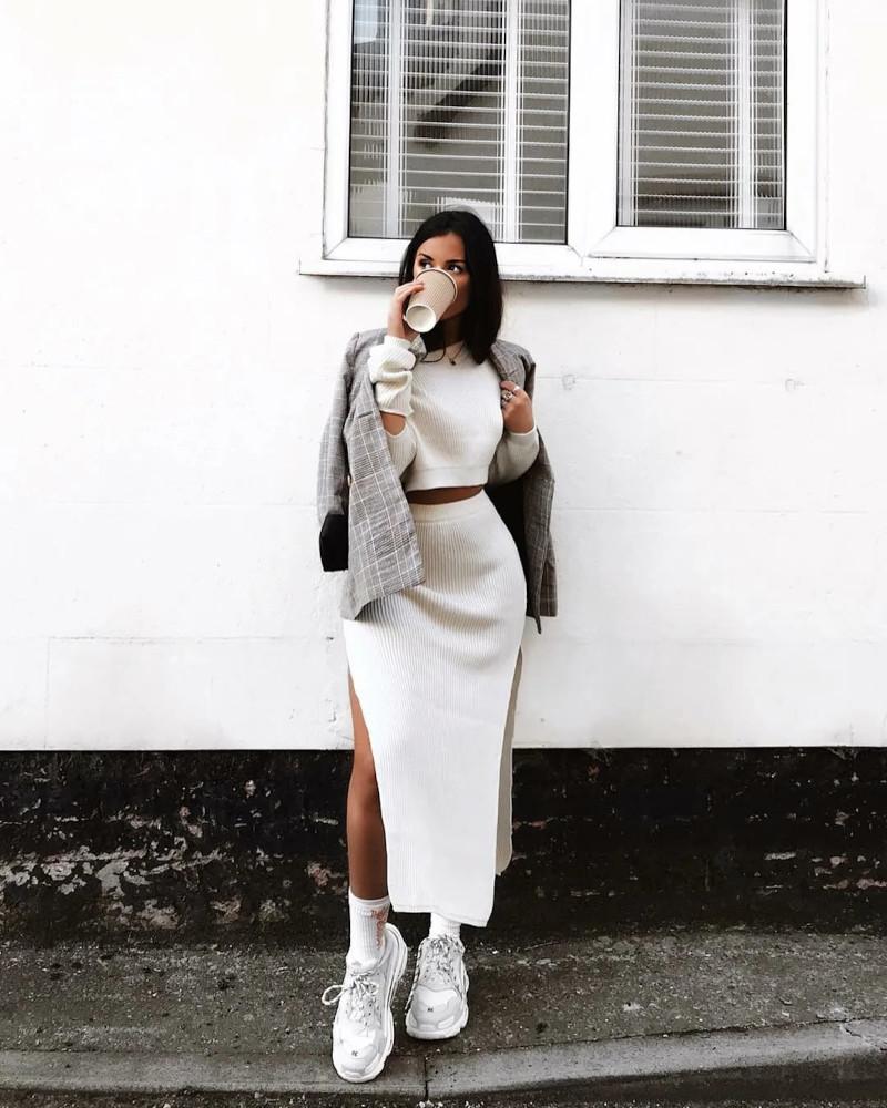 ensemble jupe et haut chic blanc associé avec des baskets blancs et blouson gris