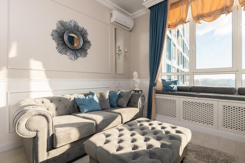 fauteuil et pouf assorti en gris clair capitonés au style classique coussins bleus