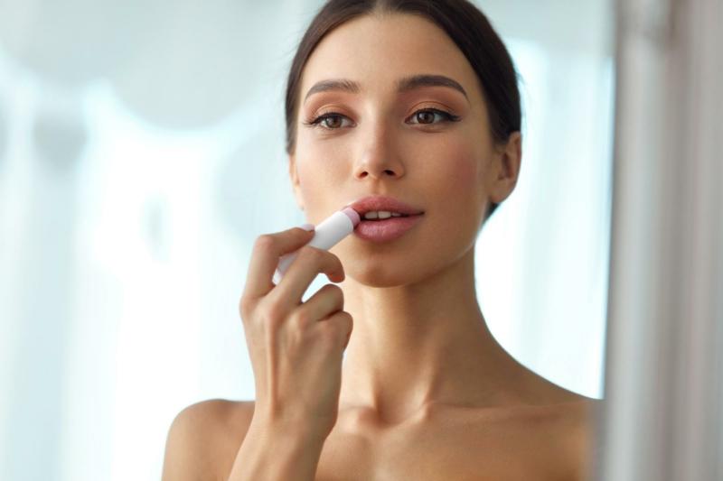 huile de ricin levre une femme qui met du baume sur ses lèvres
