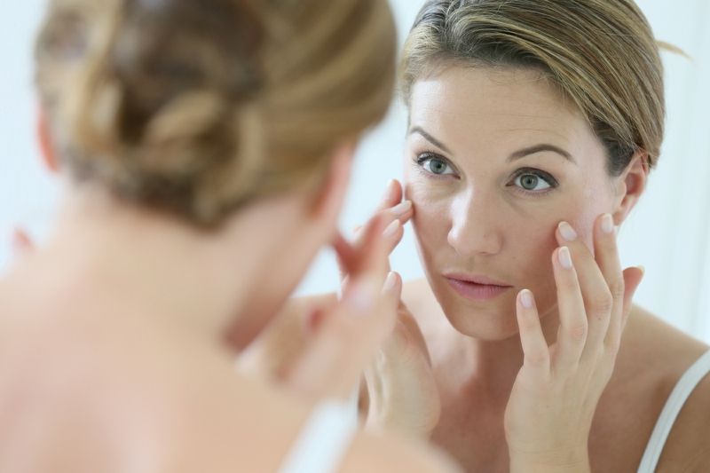 middle aged woman applying anti aging cream