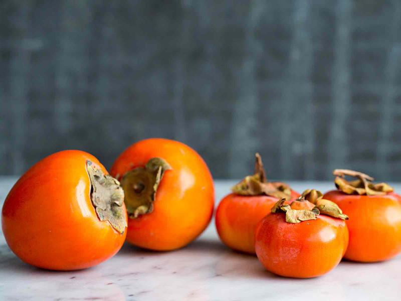 kaki fruit plein de bienfaits pour la santé mur anthracite et plan de travail gris clair