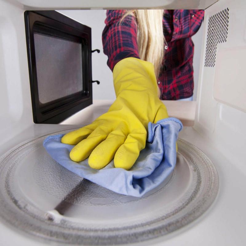 nettoyer micro onde une femme qui nettoie le micro ondes à l aide d une éponge