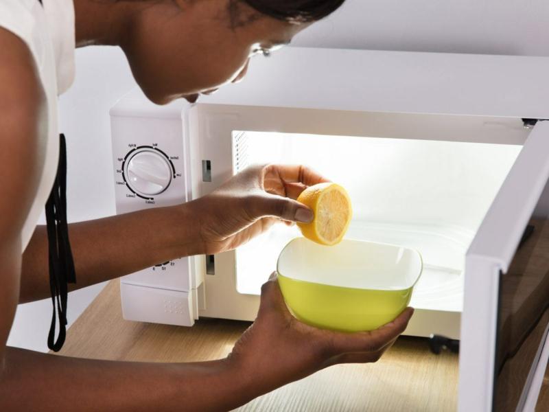 nettoyer micro onde une femme qui nettoie le micro ondes à l aide du citron