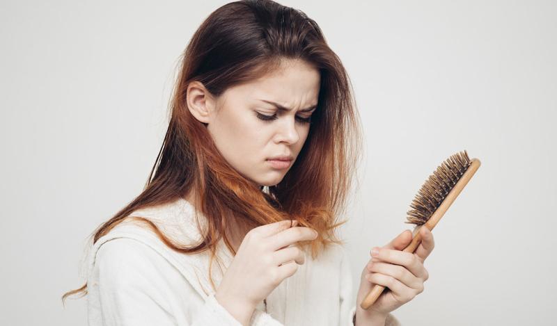 perte cheveux femme une femme mécontente qui peigne ses cheveux