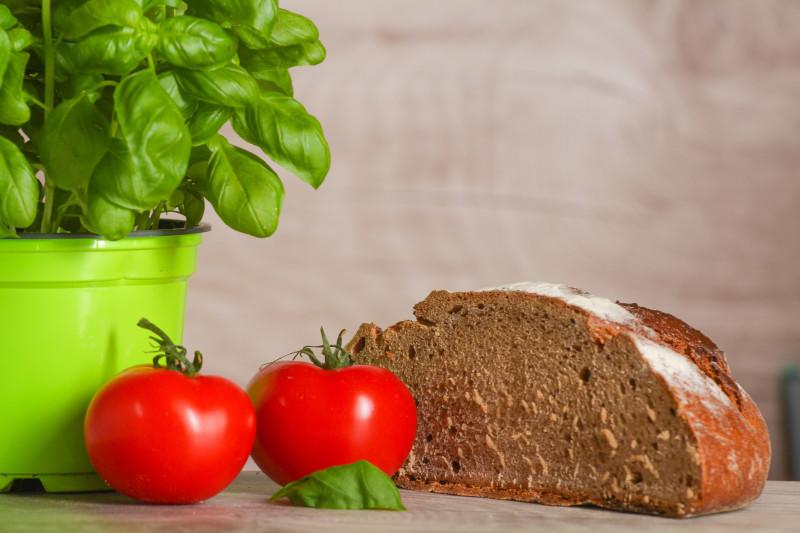 petit dejeuner keto pain bis coupé en deux deux tomates pot de basilic sur un plan de travail en bois