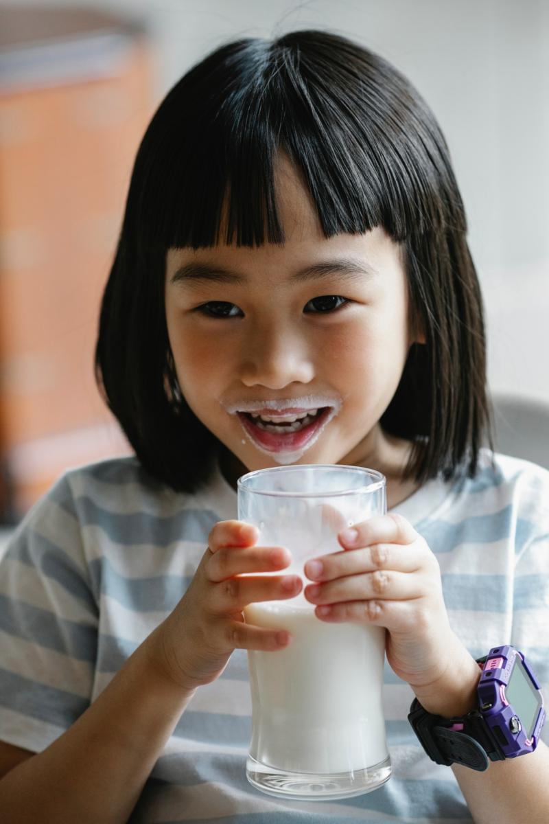 poche sous les yeux une petite fille qui boit du lait