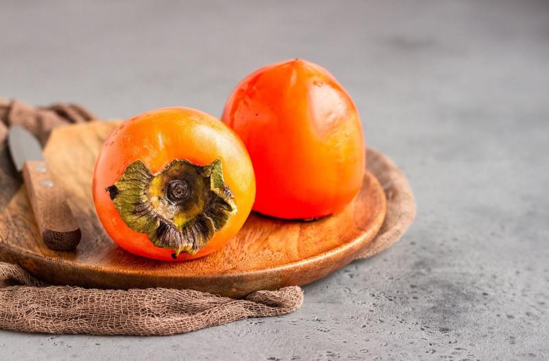 pomme kaki deux fruits mûrs en orange vif sur une planche en bois
