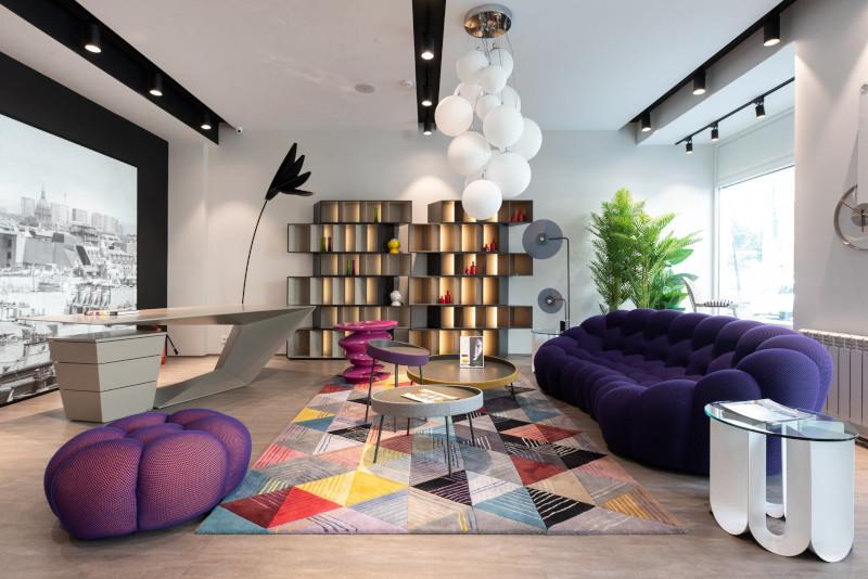 pouf design luxe salon moderne en coleurs canapé bleu foncé tapis multicolore pouf violet