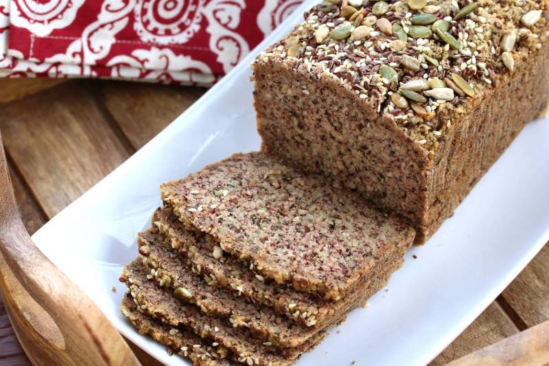 recette pain keto aux graines tranché dans une assiette de service blanche