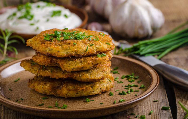 rosties pomme de terre pile de galettes saupoudrées d oignon nouveau garnies de yaourt aux herbes