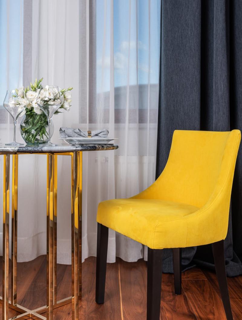 salons tendance 2021 chaise tapissée en jaune rideau en bleu foncé en contraste