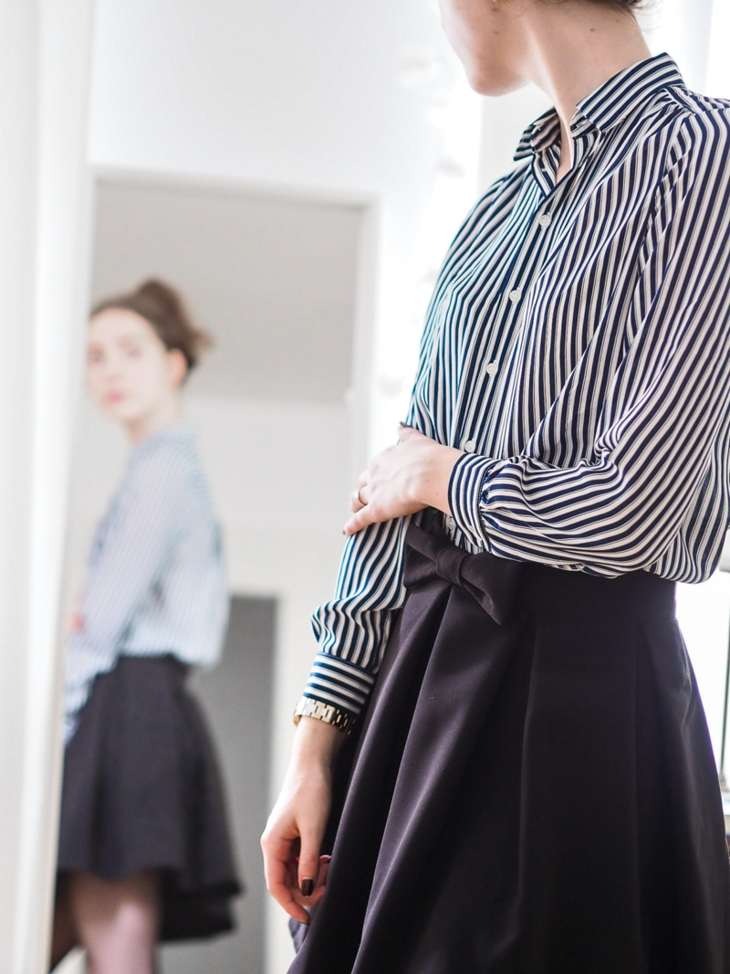 style classe femme une chemise noire et blanche rentrée dans une jupe dans le miroir