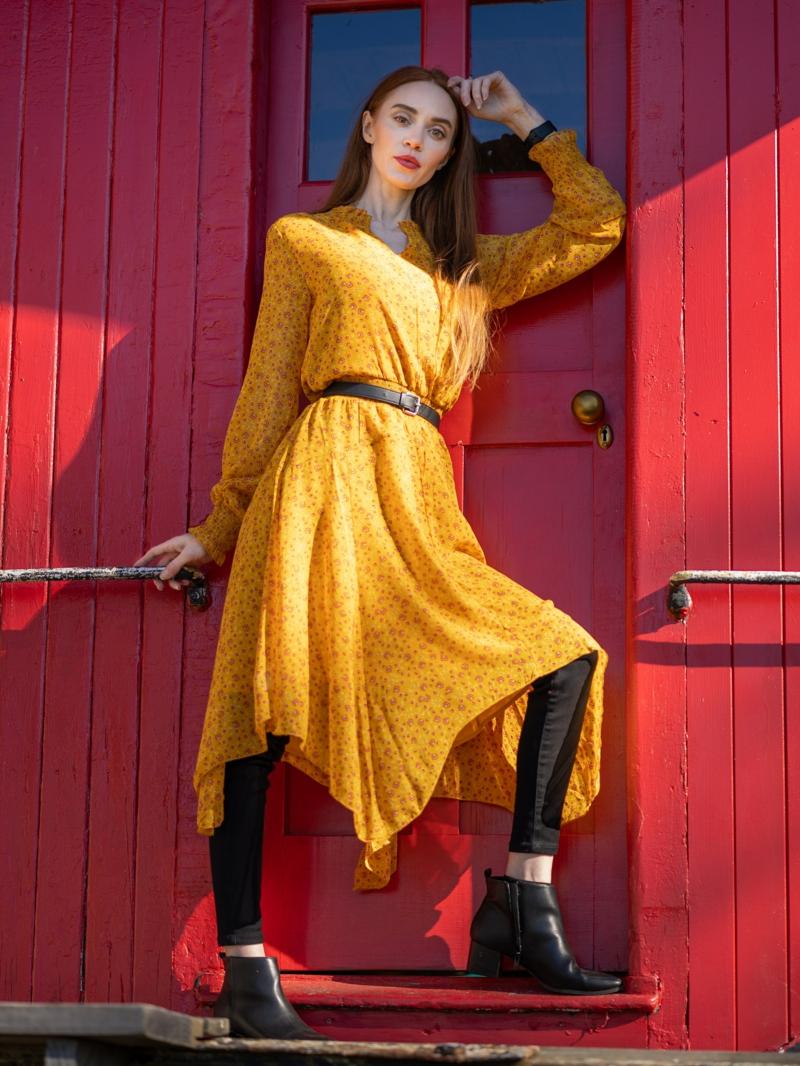 tendance tenue femme une femme qui porte une robe jaune au dessous des jeans noirs copy