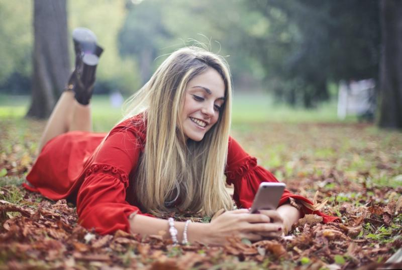 tendance tenue femme une fille qui porte une robe rouge allongée sur les feuilles tombées copy