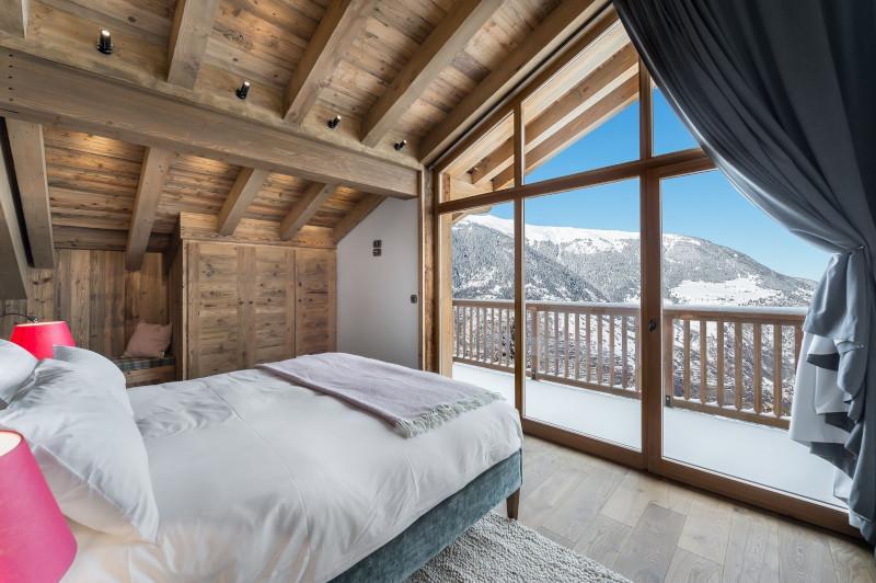 chambre chalet linge de lit blanc murs en bois portes fenetres avec vus splendide