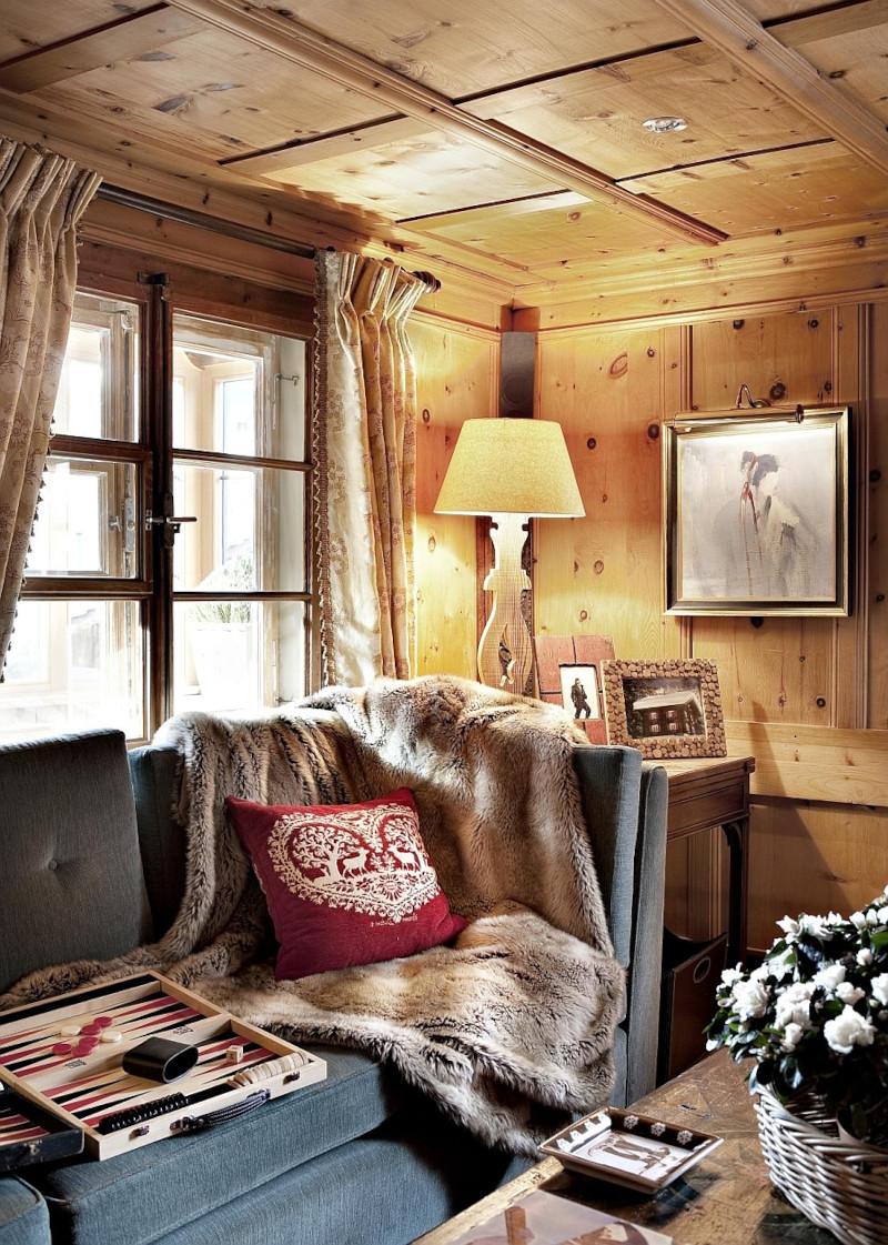 chambre style chalet chic canapé en gris foncé plaid en fourrure beige coussin en bordeaux
