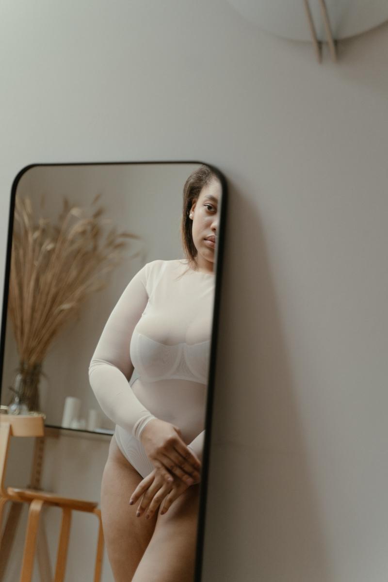 eliminer la cellulite une femme qui se regarde dans le mirroir
