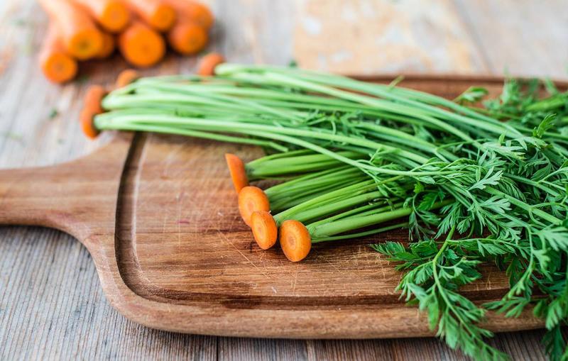 fanes de carottes les feuilles séparées des carottes sur une planche de bois