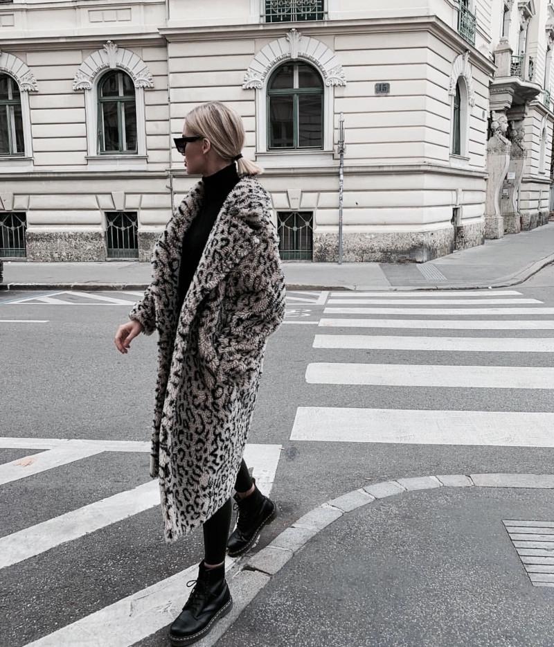 haut femme tendance manteau en fausse fourrure et tenue noire femme aux cheveux blondes