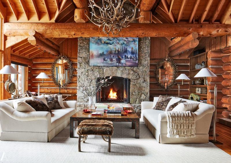 interieur chalet rustique canapés en gris clair cheminée en pierre brute tapis blanc