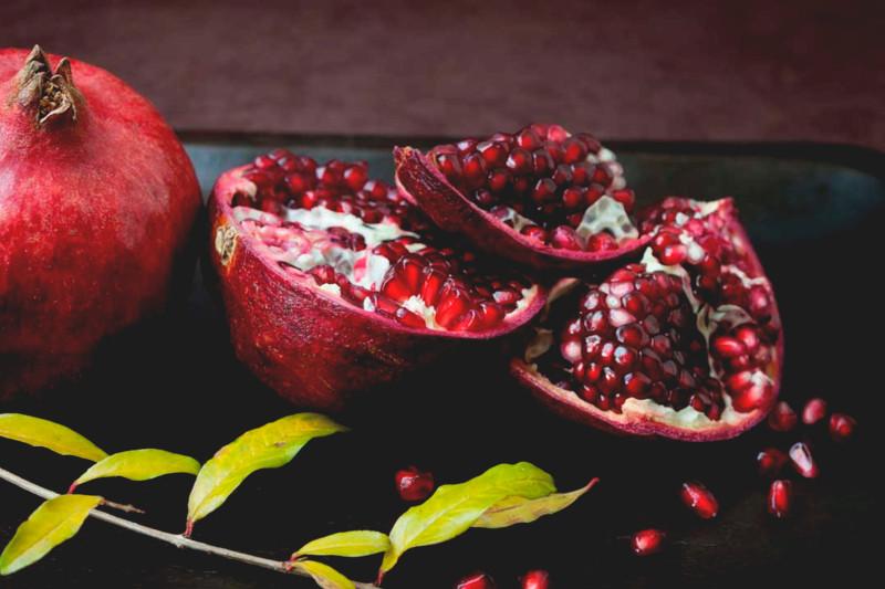 manger de la grenade fruit coupé en quartiers bon pour la digestion et la perte de poids