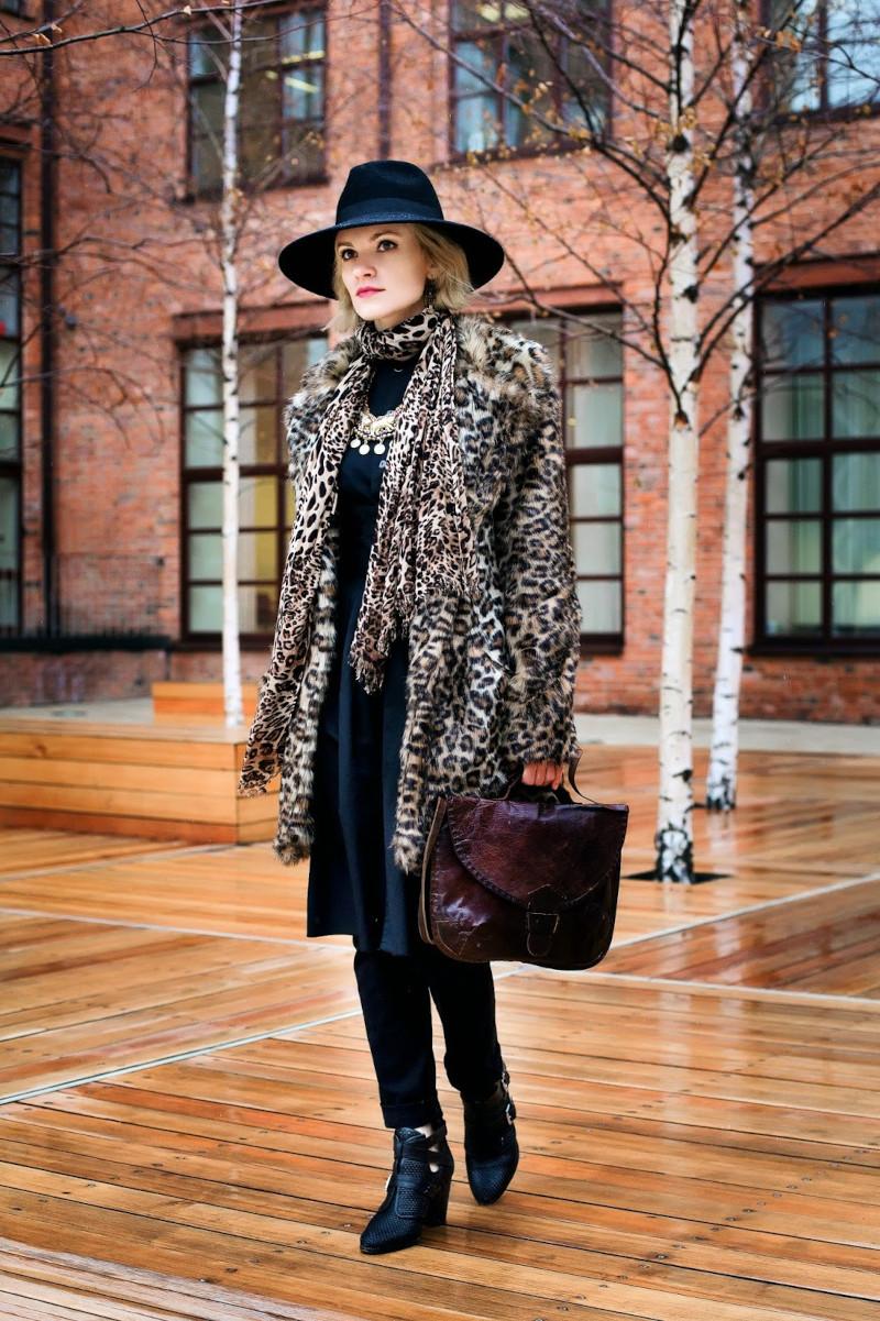 manteau léopard femme à la tenue chic en noire chapeau à bords noir bottines noires