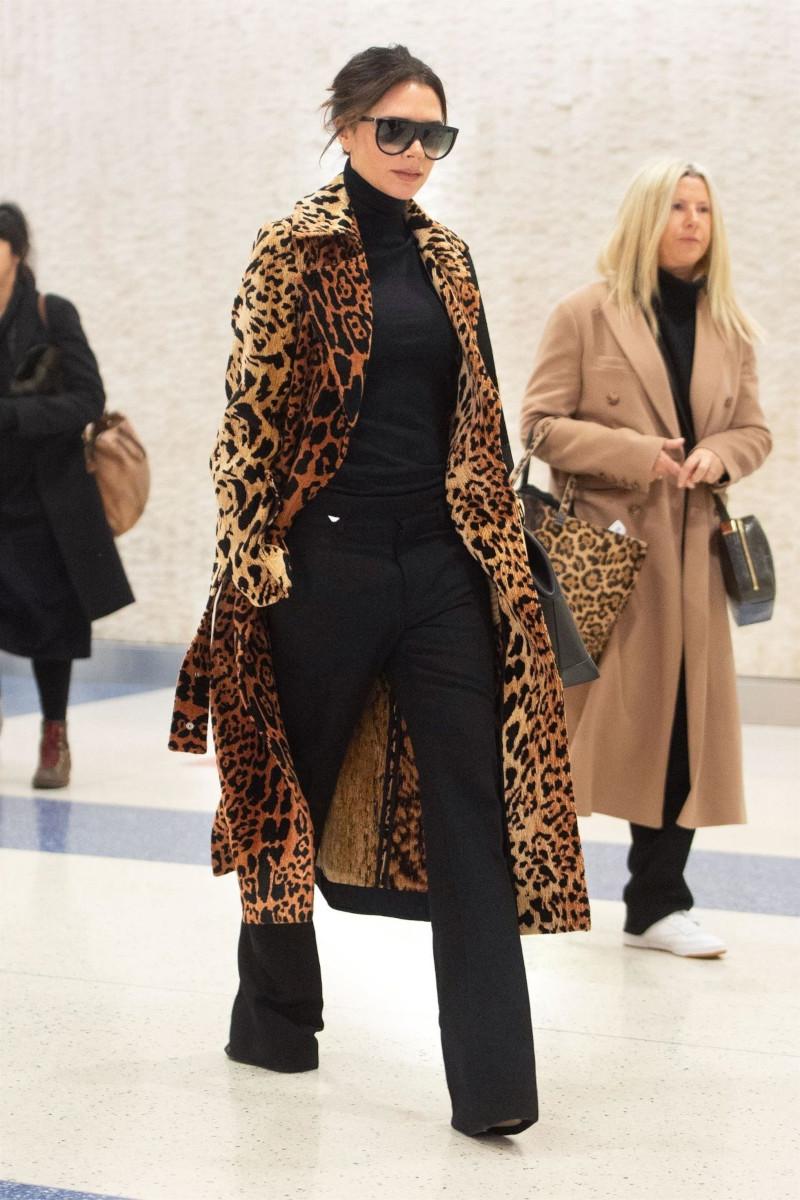 manteau tendance victoria beckham en tenue noire avec manteau léopard lunettes de soleil noires