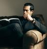 montre de luxe homme vetu en costume habillé noir un canape en cuir